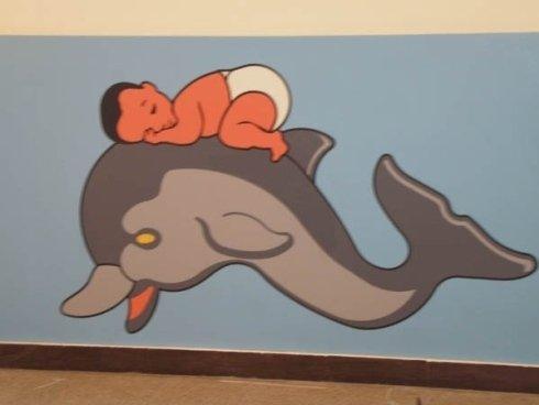 rappresentazione di neonato che dorme su un delfino