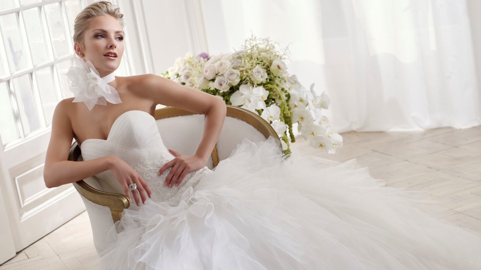 una donna con un abito da sposa e accanto dei fiori
