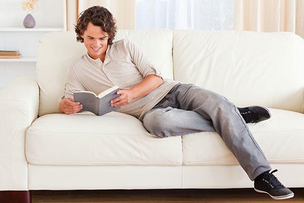 ragazzo legge su divano bianco in pelle ad ancona