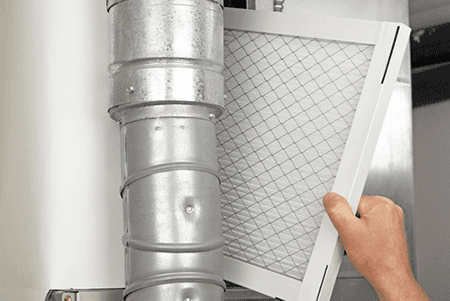 A male's arm holding a filter for HVAC installation and maintenance.