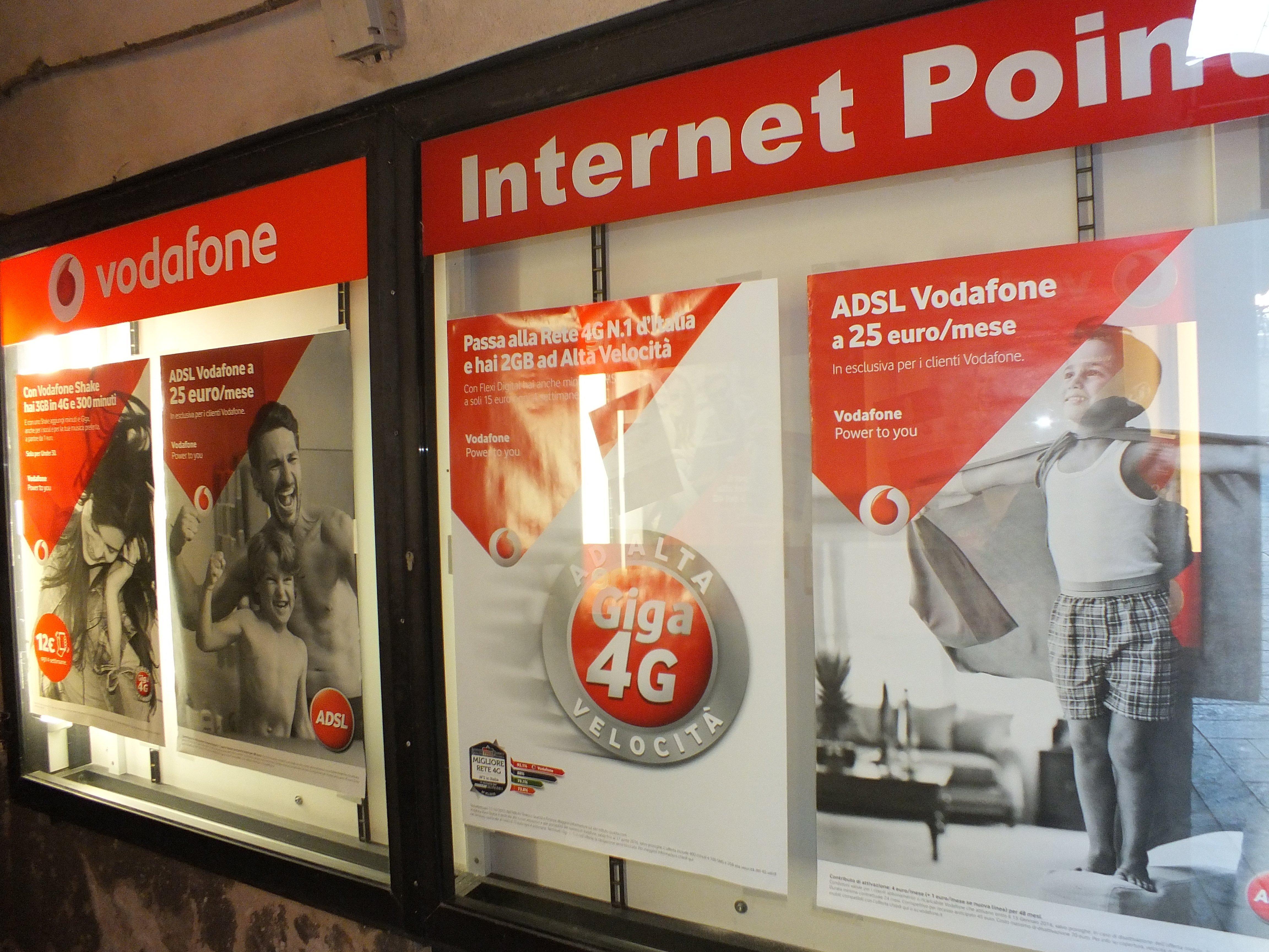 vetrina con scritto Vodafone Internet Point con delle brochure che spiegano i piani tariffari relativi a interneta Varazze, SV