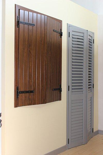 una finestra con le ante di legno chiuse e un'altra con delle persiane grigie