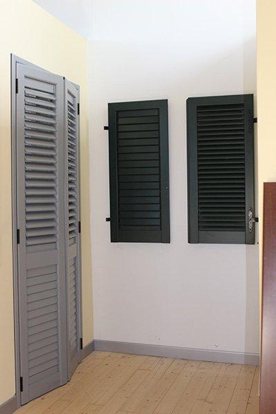 una finestra con delle persiane grigie e una con delle ante delle persiane verdi scure