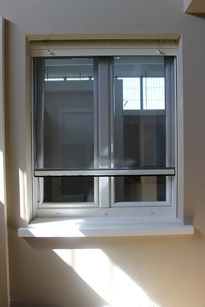 una finestra con la zanzariera abbassata a metà