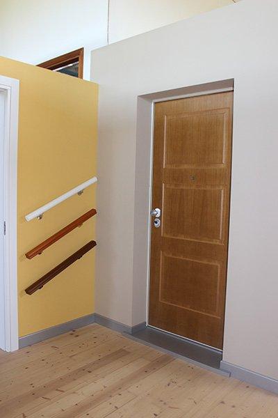 una porta in legno e accanto dei corrimani di diversi colori