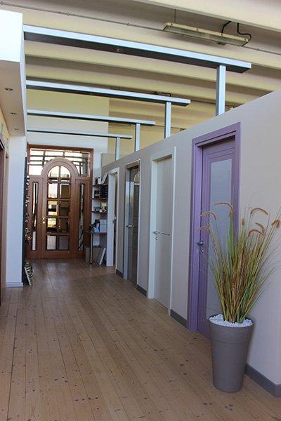 delle porte bianche e viola, bianche e una in legno con dei vetri