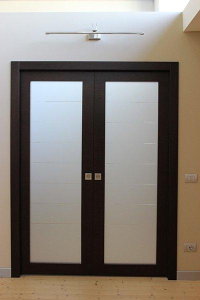 una porta in vetro e legno scuro a due ante