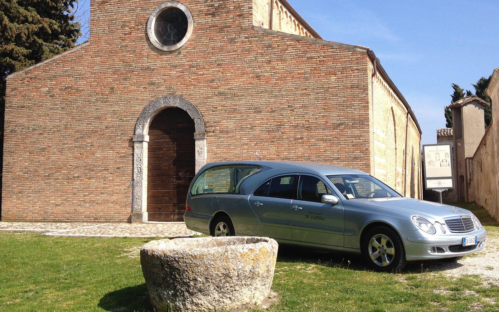 Un auto funebre grigria davanti una chiesa