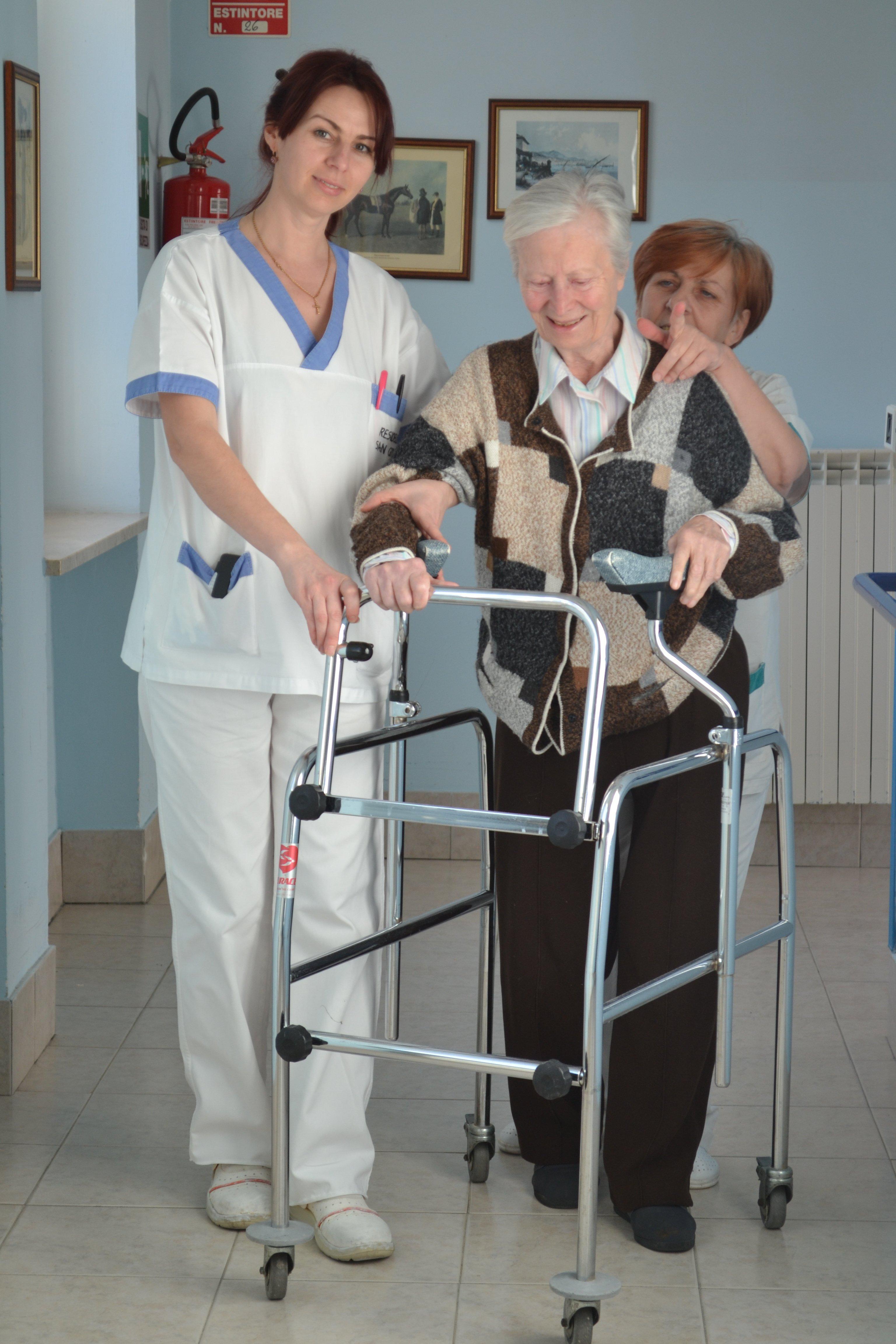 persona anziana assistita da due infermiere per fare attività motoria