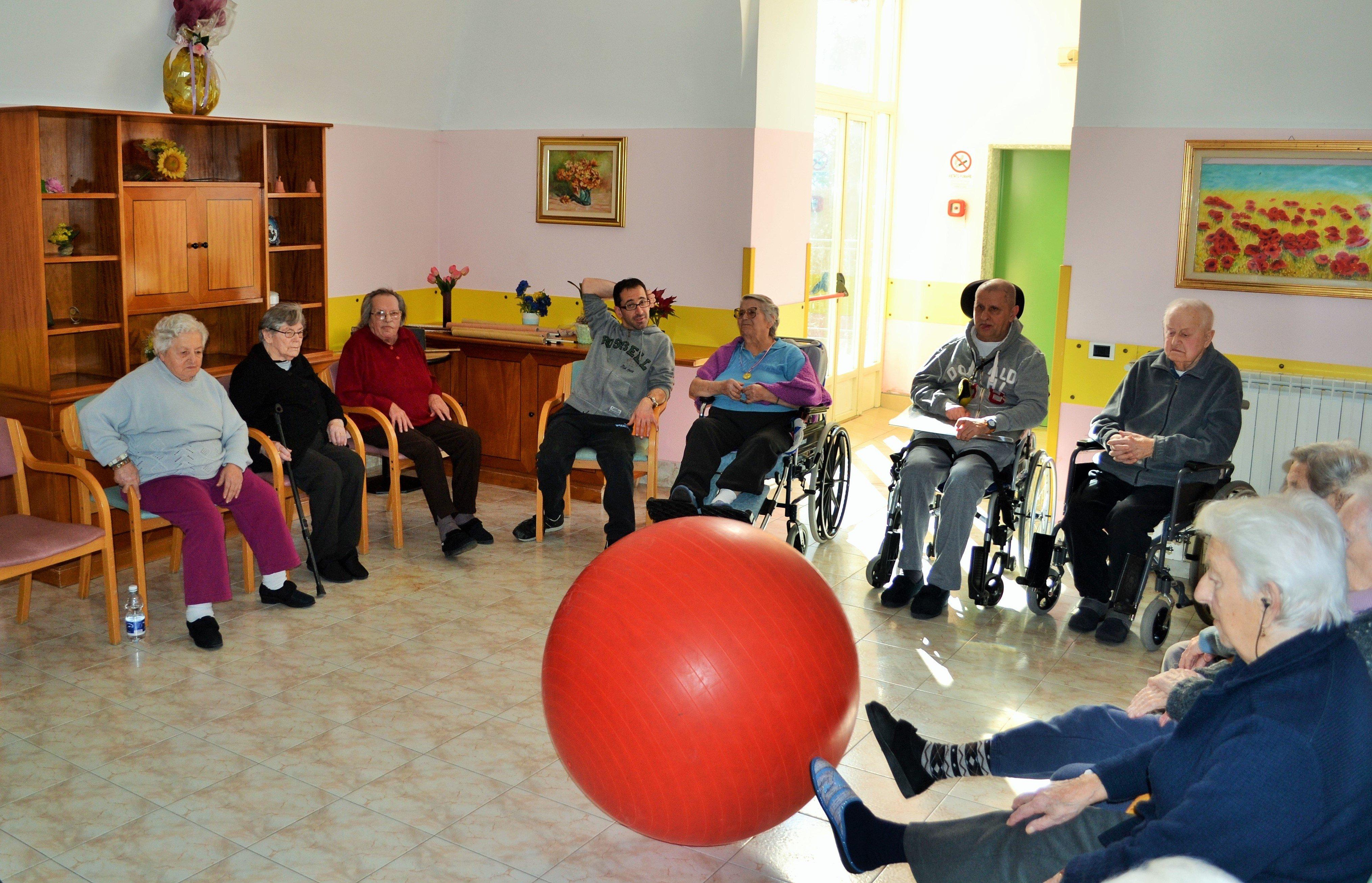 gruppo di anziani in cerchio con palla rossa al centro