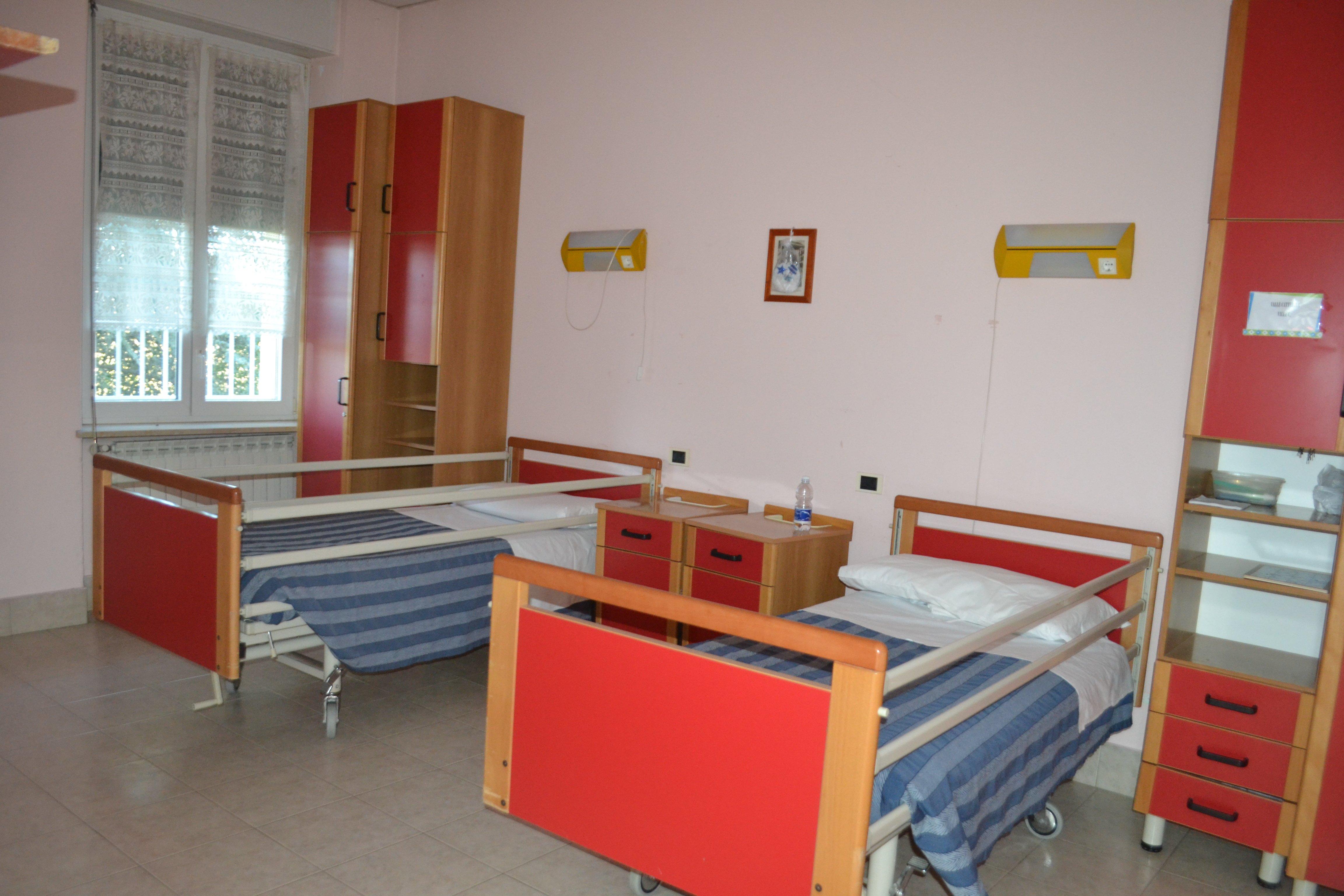 camera con due letti rossi e ramdiuo