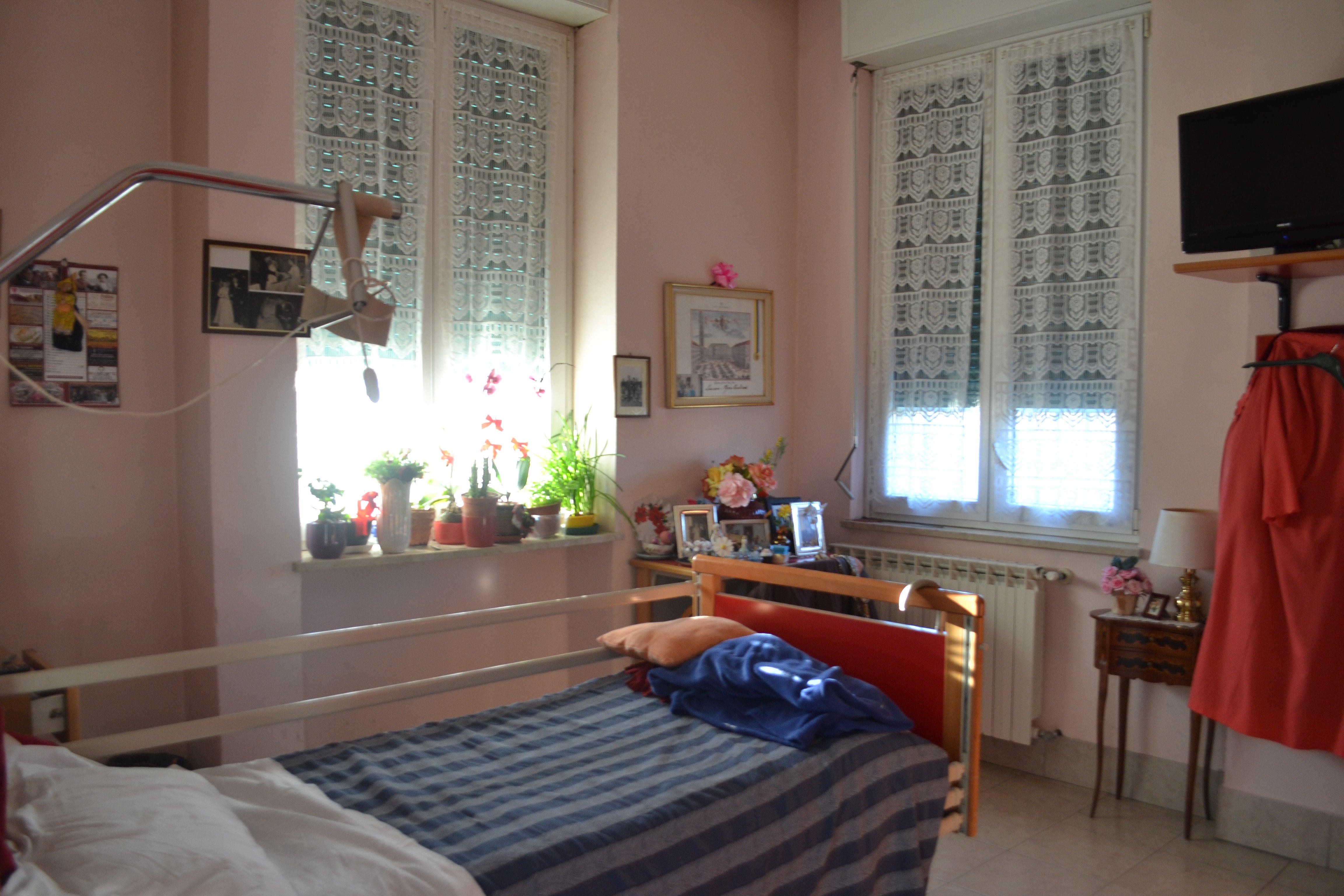 camera con letto accando a due finestre