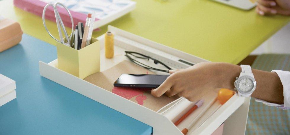mano che appoggia il cellulare sulla scrivania