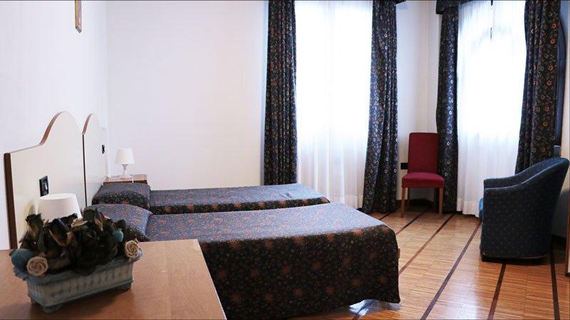 una camera da letto con due letti singoli,una poltrona e una sedia rossa