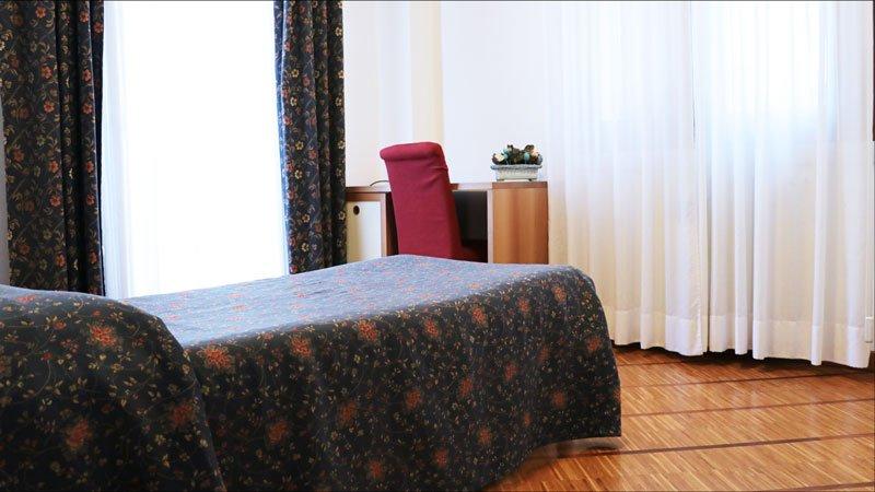 vista ravvicinata di un letto singolo e una piccola scrivania con una sedia rossa