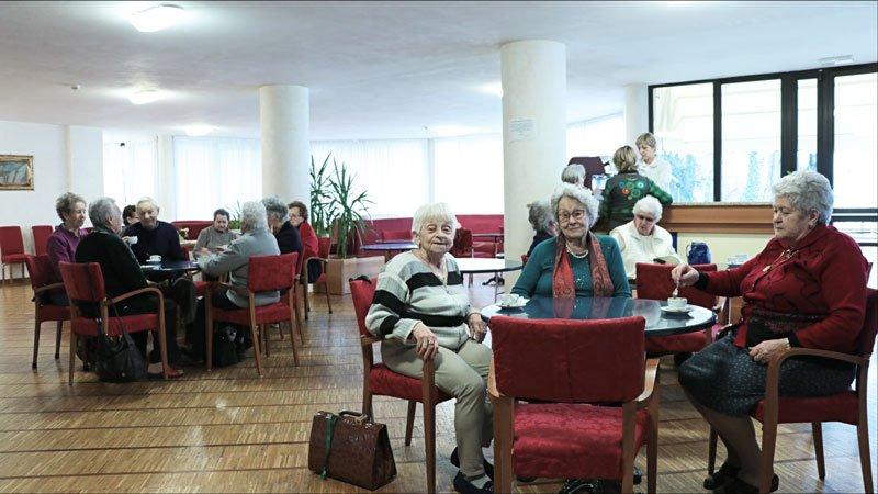 delle persone anziane sedute a dei tavoli