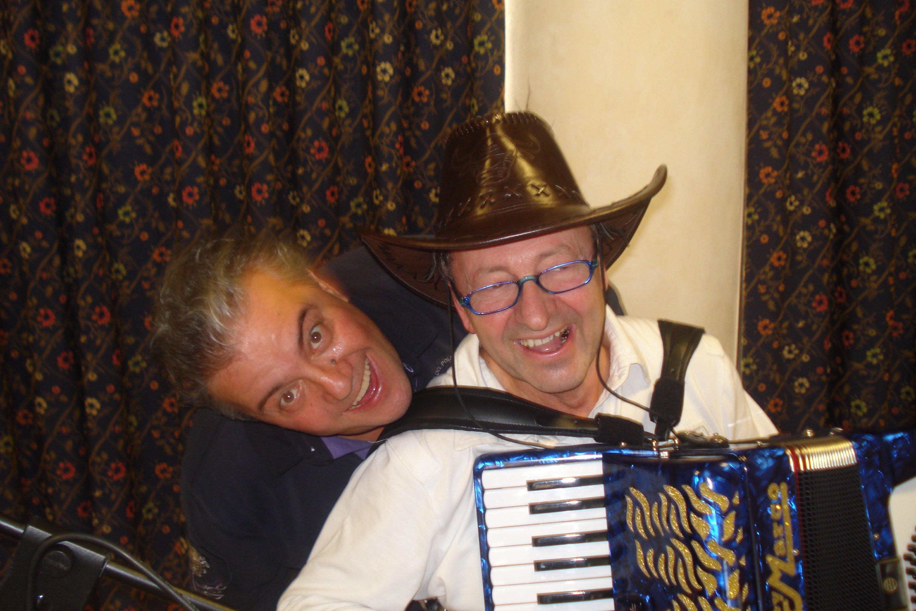 Un uomo suona una fisarmonica e un altro sorride alle sue spalle