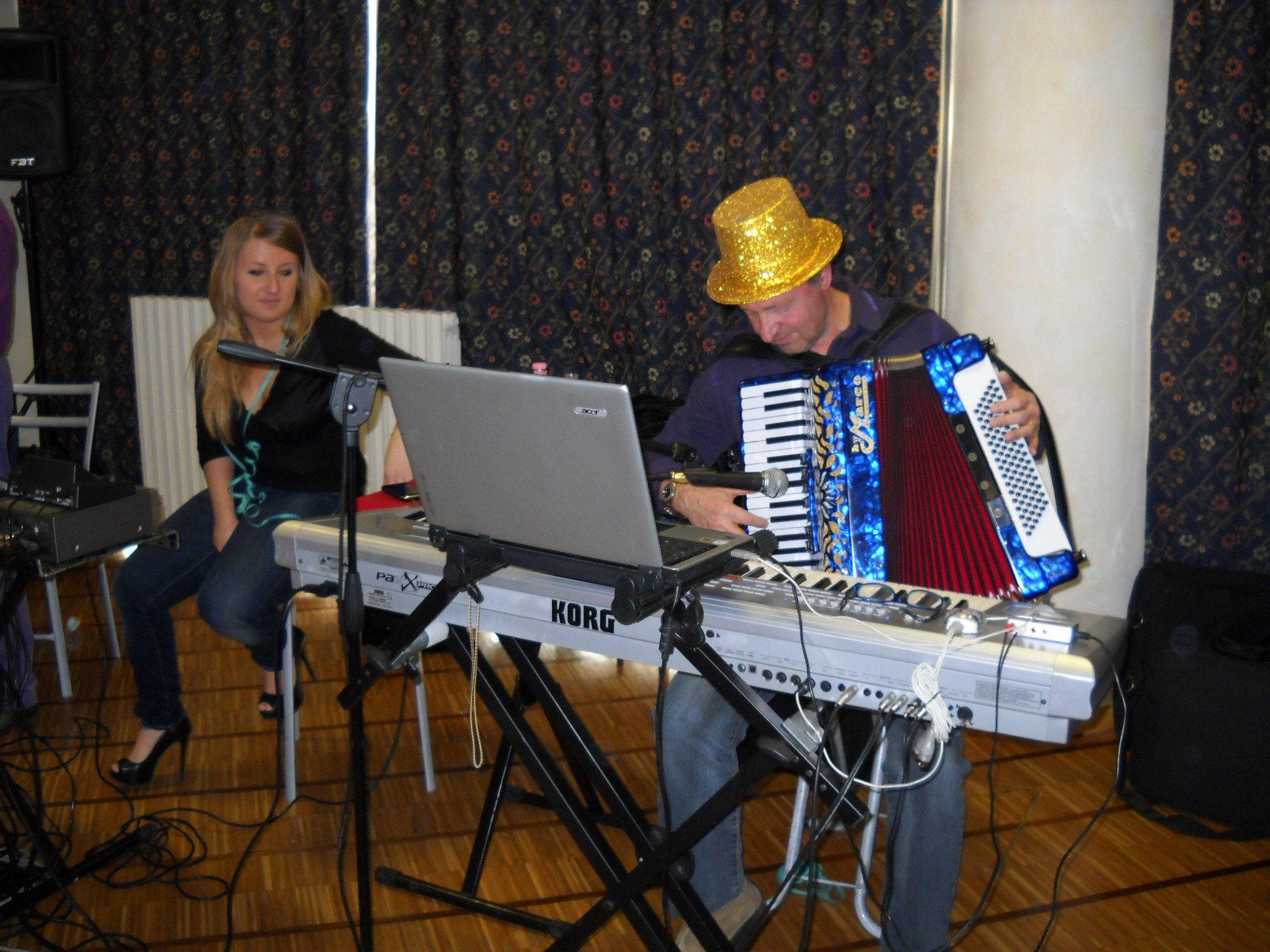 Un uomo suona la fisarmonica di fronte a una pianola e accanto una donna vicino a un microfono