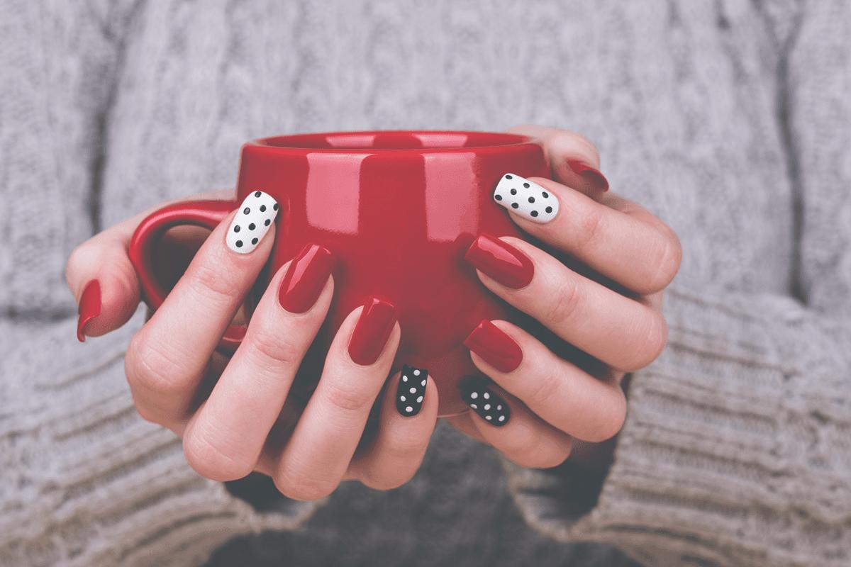 mani con nail's art che sorreggono una tazza rossa