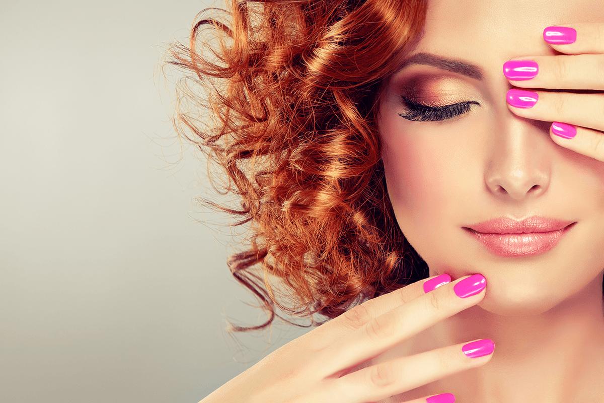 Donna dai capelli rossi con smalto alle unghie rosa
