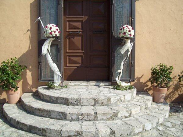 decorazioni con rose bianche e rosse all'ingresso della chiesa