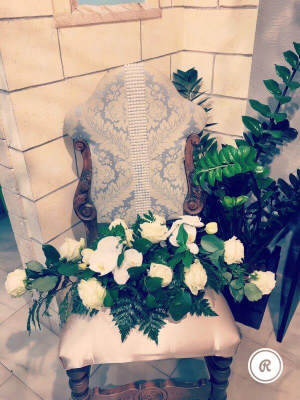 rose bianche e felce su poltrona