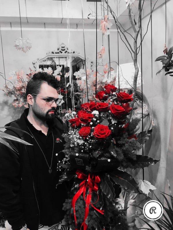 negoziante con bouquet di rose rosse