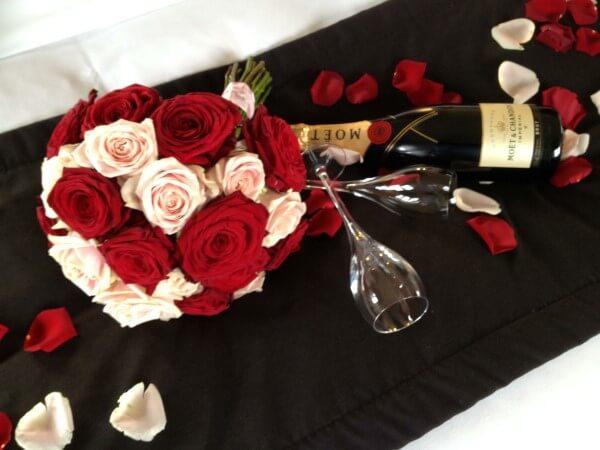 rose rosse e bianche su tavolo con champagne