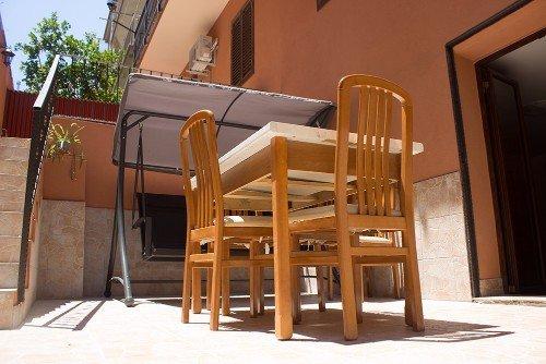 una terrazza con un tavolo e un divano a dondolo