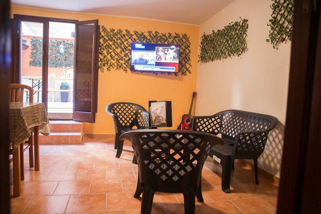 un divano, due sedie di plastica e una tv al muro