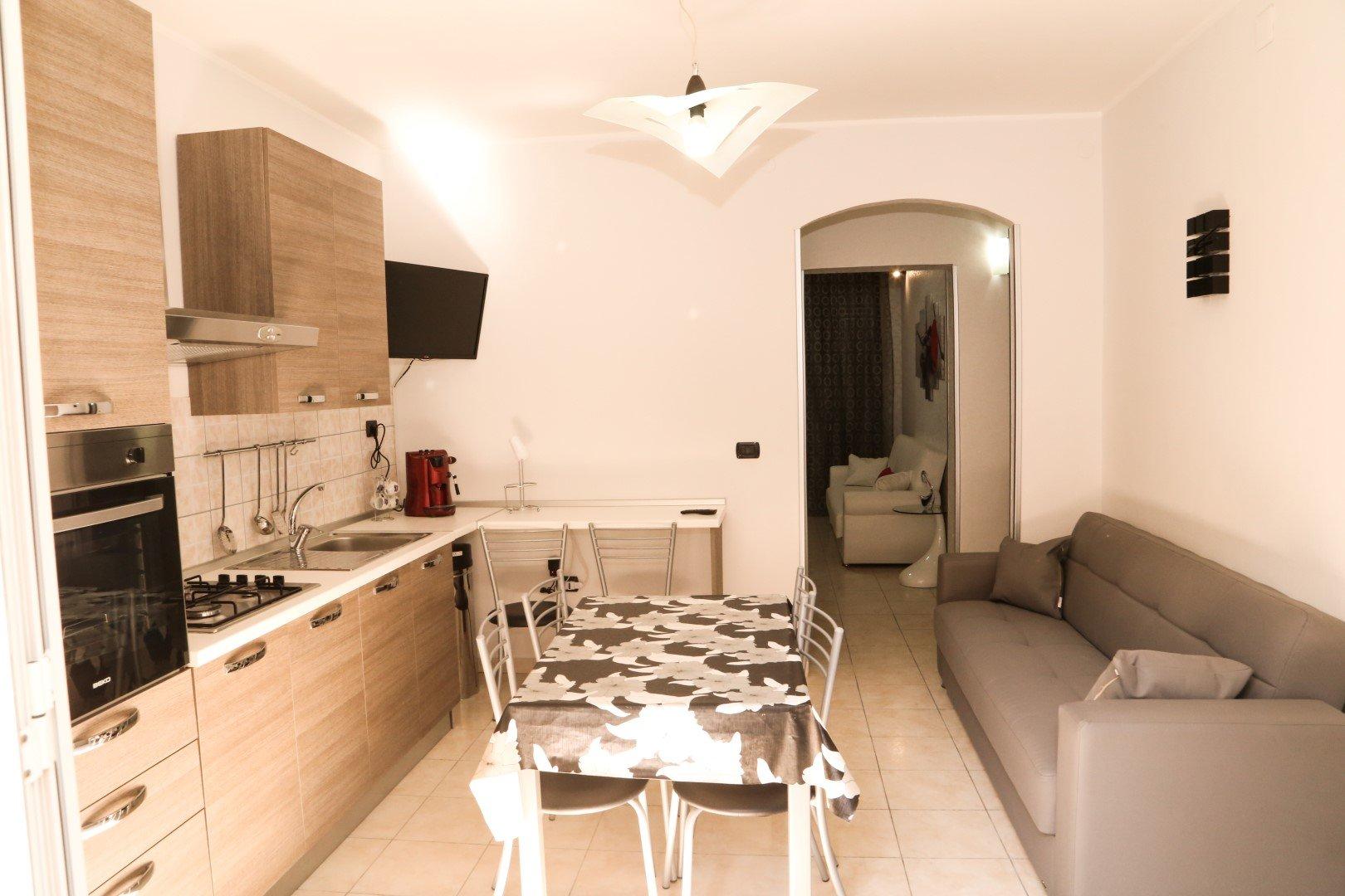 una cucina in legno chiaro, un tavolo e un divano
