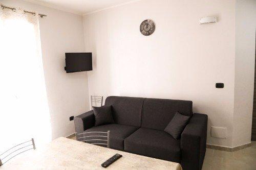 una sala con un divano nero e un tavolo
