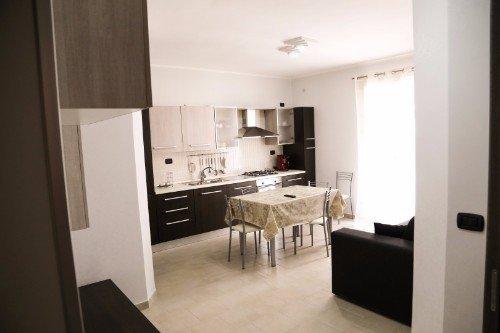 una cucina a blocco con un tavolo e un divano nero