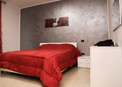 una camera con un letto e un comodino bianco