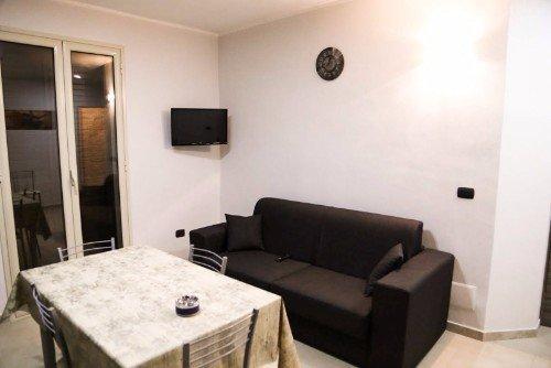 una sala con un divano nero, una Tv al muro e un tavolo