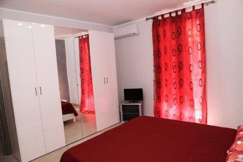 una camera con un letto matrimoniale e un armadio bianco con due specchi