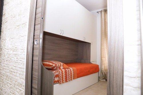 una cameretta con letto singolo e armadio in legno