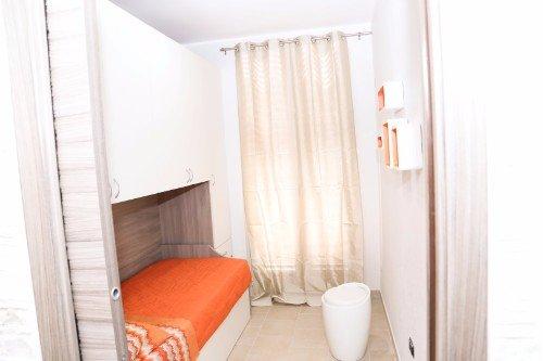 una cameretta con un letto singolo, armadio e uno sgabello bianco