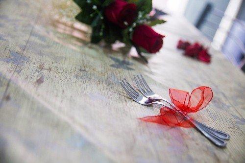 un tavolo con delle rose e due forchette legate con un fiocco rosso
