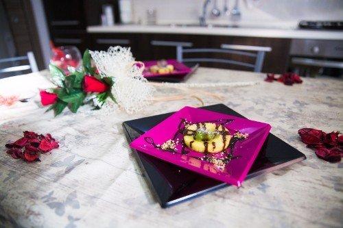 un tavolo con delle rose e dei piatti di dolci