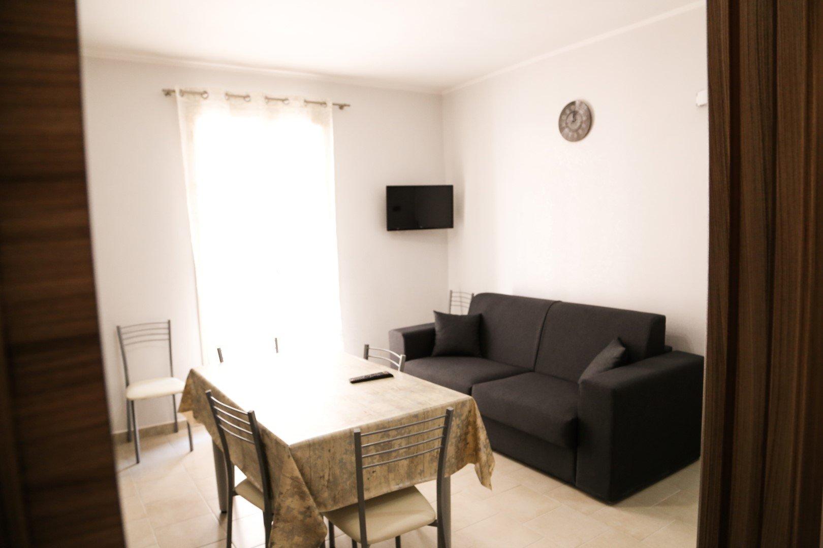 una sala con un divano, un tavolo e una Tv