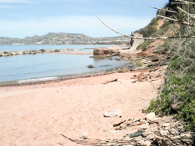 una spiaggia sabbiosa e scogli in lontananza