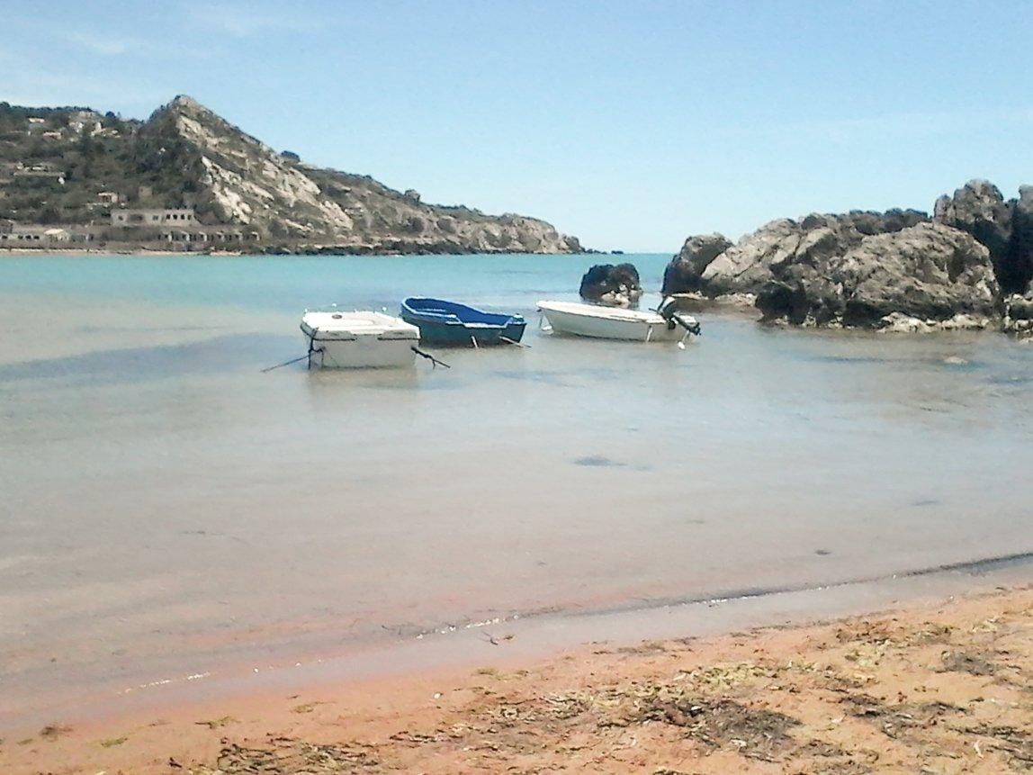 tre barche vicino la riva del mare