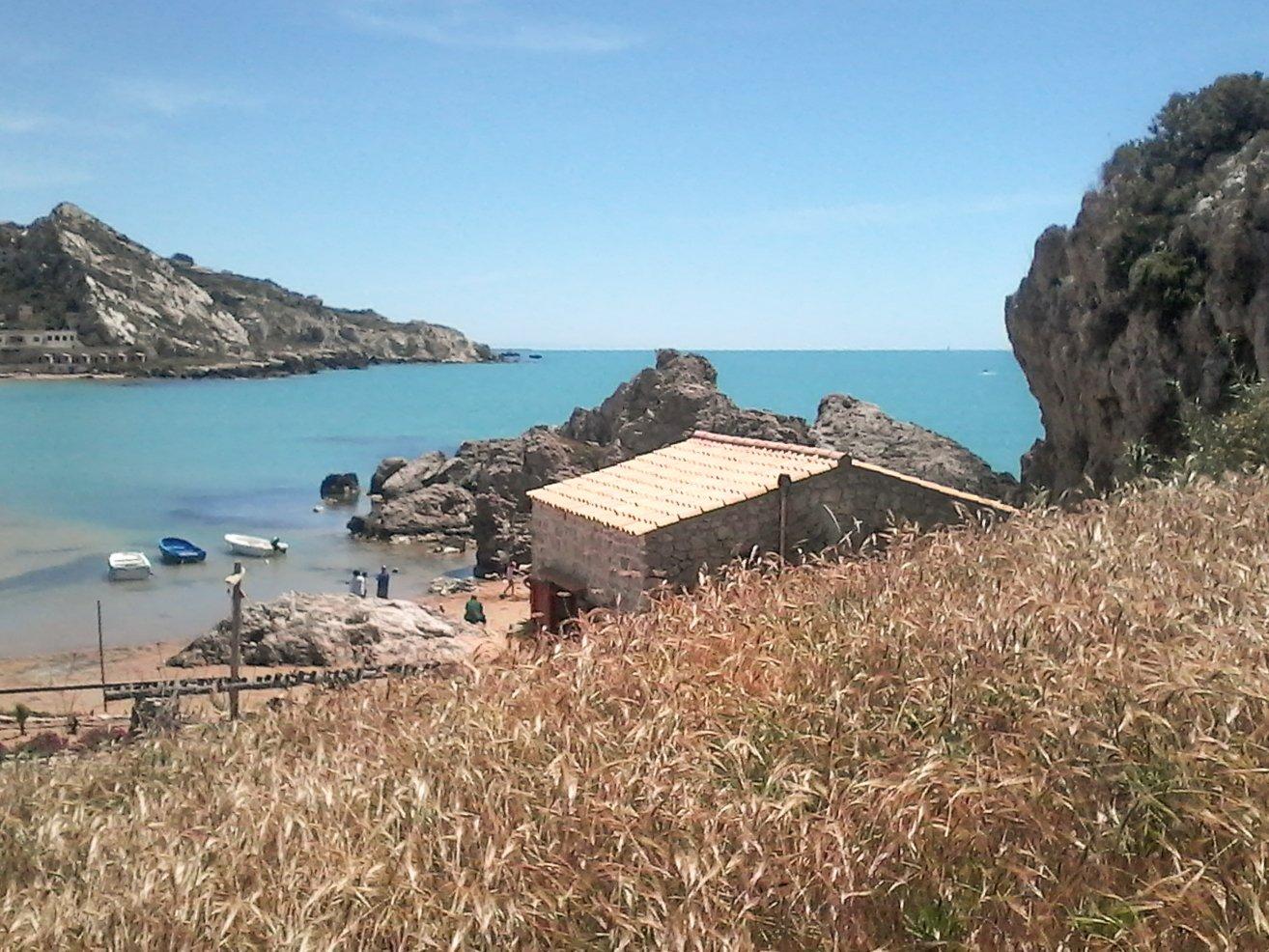una casa e vista di una spiaggia con gli scogli e delle barche