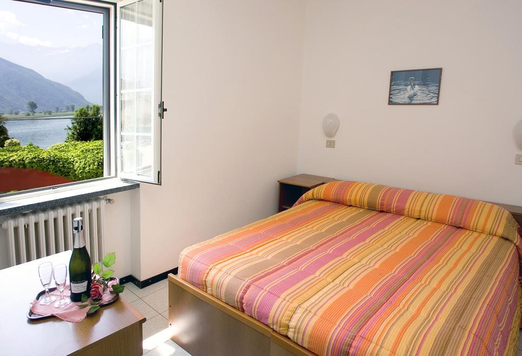 una camera con le finestre aperte e vista di un lago