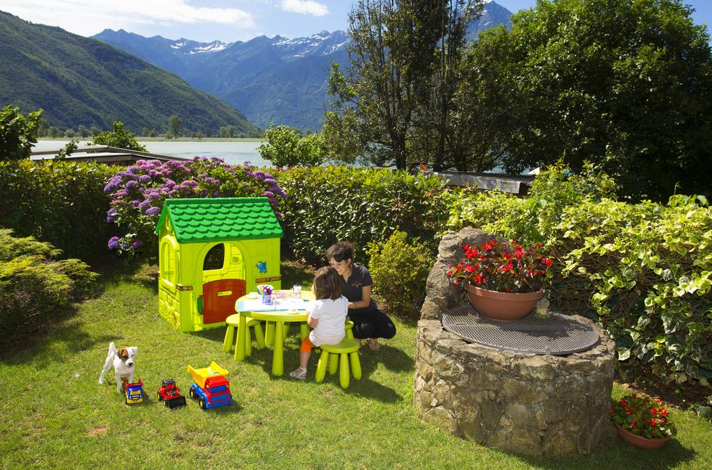 una bambina e una donna mentre dipingono dei disegni in un giardino con vista di un lago