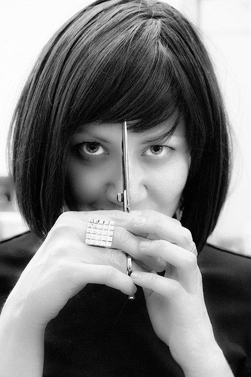 donna con forbici in mano si taglia la frangia