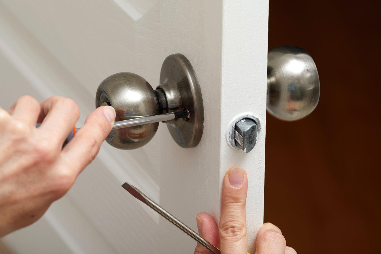 persona che fissa con un cacciavite la serratura della porta