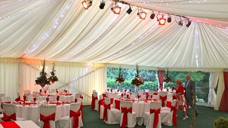 white chairs with red ribbon tied to it