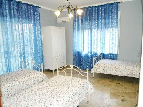 camera tripla con tende blu in casa di riposo
